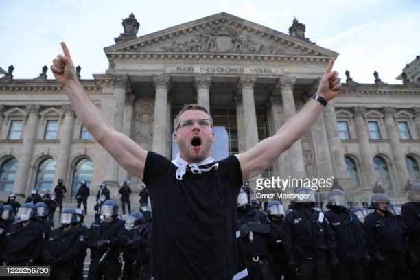 A protester gestures in from of German riot police standing guard outside the Reichstag during protests against coronavirusrelated restrictions and...