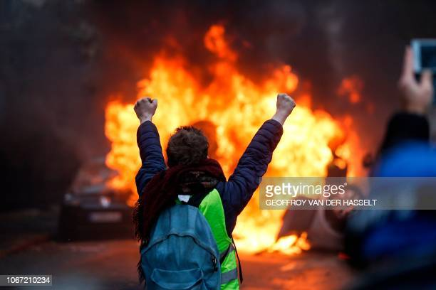A protester gestures in front of a burning vehicle as Yellow vests protesters demonstrate against rising oil prices and living costs in the French...
