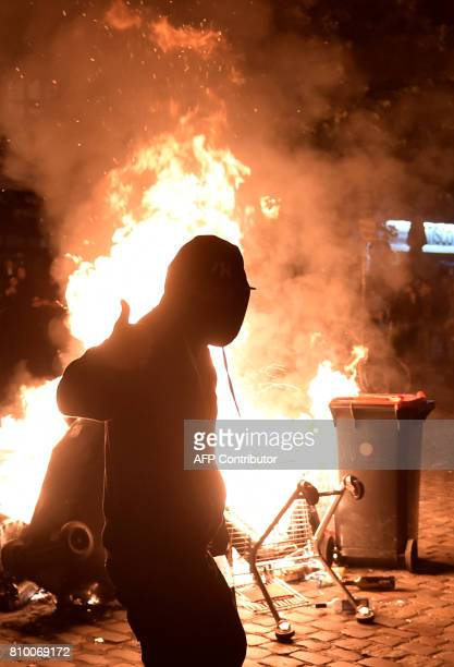 A protester gestures in front of a fire after the 'Welcome to Hell' rally against the G20 summit in Hamburg northern Germany on July 6 2017 German...