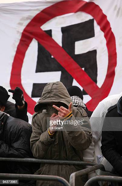 A protester gestures in front of an antifascist banner as he campaigns against a demonstration organised by the group 'Stop the Islamisation of...