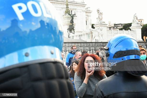 Protester gestures in provocation to police officers in provocation in Rome on November 15 during a demonstration of anti-mask supporters and against...