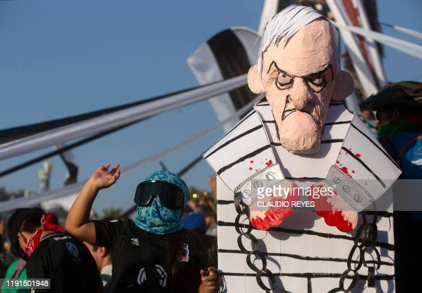 A protester gestures next to a figure representing Chilean President Sebastian Pinera during the first protest of the year against the government in...