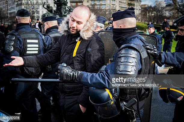 A protester gestures next to a riot police officer on the Place de la Nation in Paris on February 9 during a demonstration by nonlicensed private...
