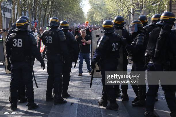 A protester gestures to anti riot police during a demonstration on April 19 in Paris as part of a multi branch day of protest called by French unions...