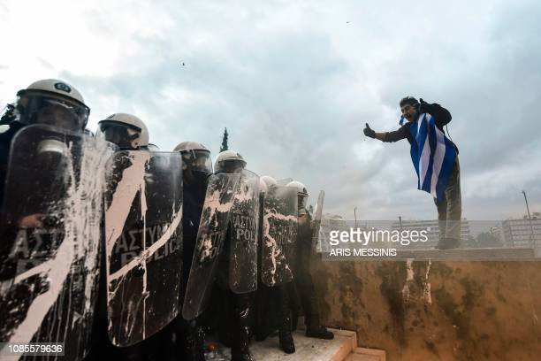 A protester gestures to riot police in front of the Greek Parliament in Athens on January 20 2019 during a demonstration against the agreement with...