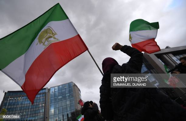 A protester gestures under a flag of the National Council of Resistance of Iran during a demonstration in support of the Iranian people amid a wave...