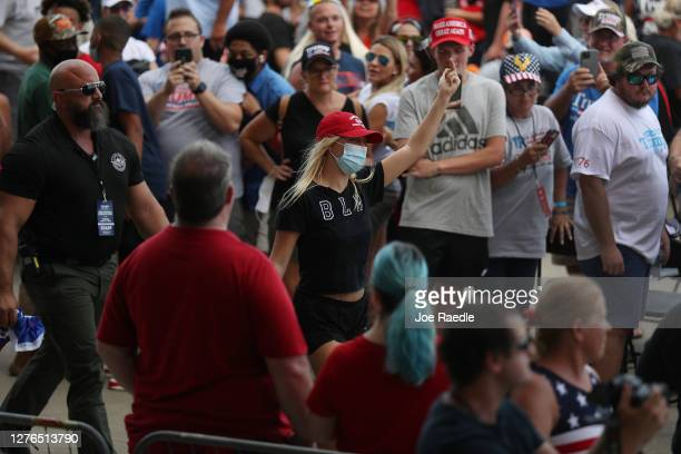 A protester gestures with her middle finger as she is escorted out before the arrival of President Donald Trump for his 'The Great American Comeback...