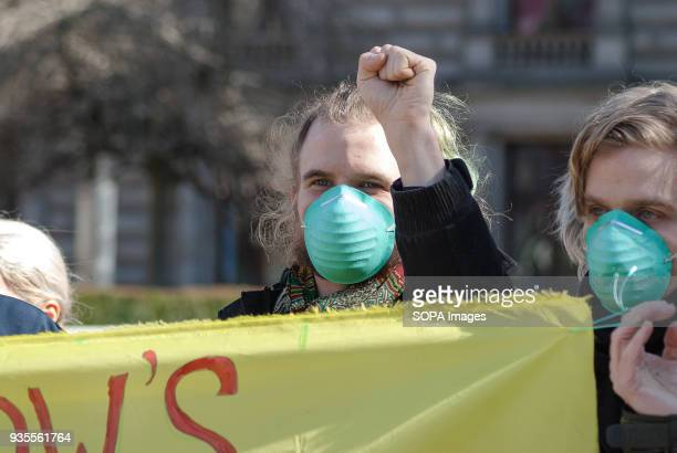A protester gestures with his hand during a protest in Glasgow's George Square in front of Glasgow City Council as he stands behind a sign that reads...