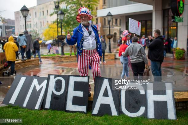 TOPSHOT A protester gives a thumbs up behind signs reading impeach as people gather outside the Target Center in Minneapolis Minnesota ahead of a...