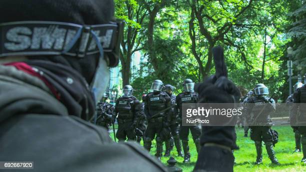 A protester gives riot police the middle finger during a free speech rally at Chapman Park in Portland Oregon on June 4 2017