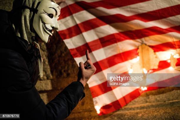 A protester gives the burning USA flag a middle finger Demonstrators attend the Annual Million Mask March bonfire night protest advertised as a...