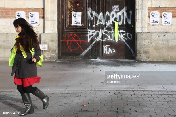 Protester grabs French President Emmanuel Macron as well as Brazilian President Jair Bolsonaro during a demonstration of the yellow vests movement in...