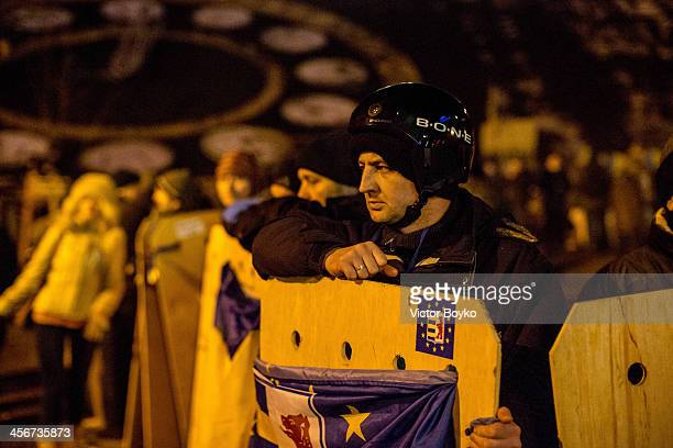 A protester guards the makeshift barricade near Instytutska street on Maidan Square on December 14 2013 in Kiev Ukraine Antigovernment protests began...