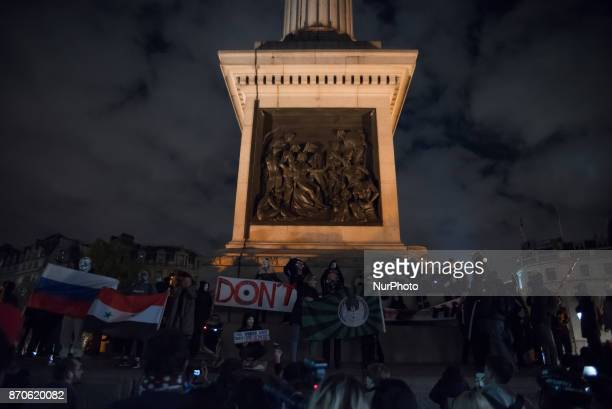 Protester have climbed the column wearing Guy Fawkes mask in Trafalgar Square during the anticapitalist 'Million Masks March' organised by the group...