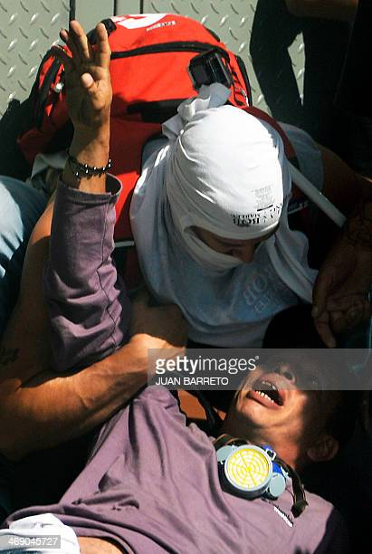 A protester helps an injured man during an opposition demo against the government of Venezuelan President Nicolas Maduro in Caracas on February 12...