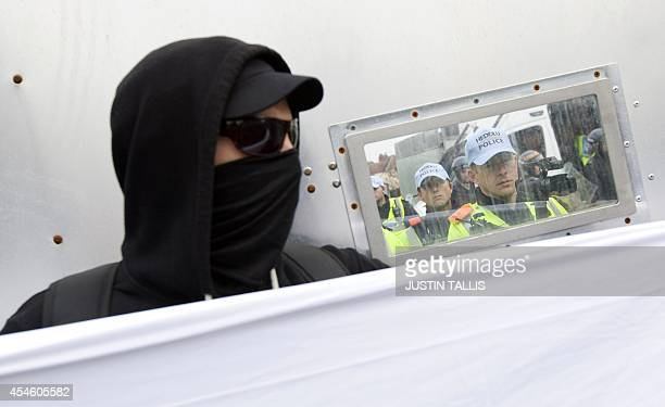 A protester hides behind a police cordon as demonstrators take part in a protest march against the 2014 NATO Summit in Newport Wales on September 4...