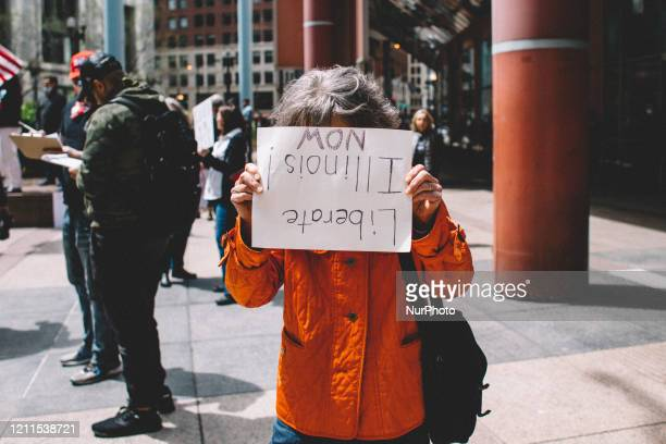 Protester hides behind her sign at the Re-Open Illinois Protest in Chicago I during protest restrictions instituted by the governor to curtail the...