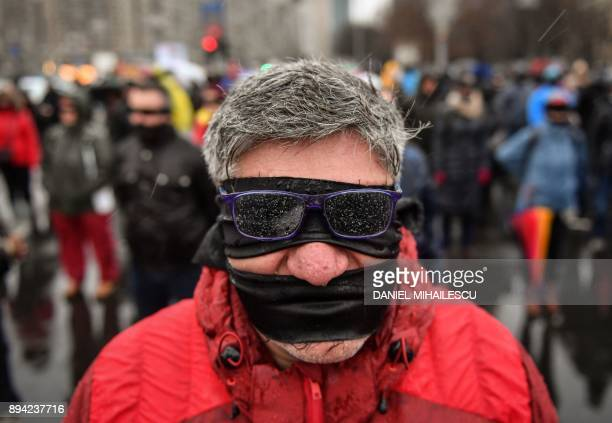 A protester his eyes and mouth covered with black cloth takes part in a silent flash mob outside the government's headquarters to denounce the...