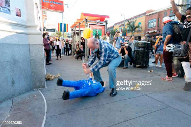 A protester hits a Donald Trump pinata as people celebrate Joe Biden being elected President of the United States in the Castro district of San...
