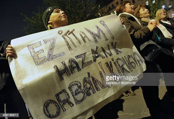 A protester hold a banner which reads 'Here is our homeland Kickout Orban' during a demo against the government's new tax plan for the introduction...