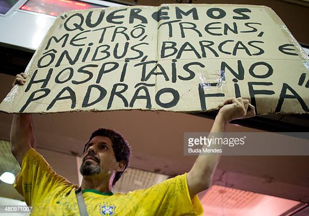 A protester hold placard during a demonstration against the 2014 FIFA World Cup Brazil at Central do Brasil train station on March 27 2014 in Rio de...