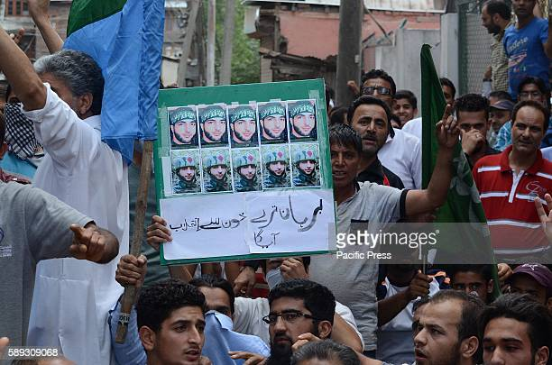 Protester hold placard praising militant commander Burhan Wani in Srinagar Government has suspended mobile services across Kashmir ahead of India's...