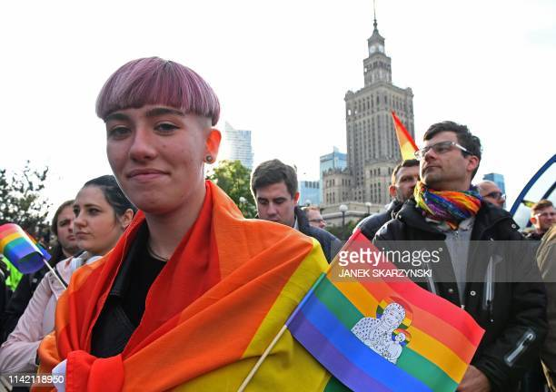Protester hold rainbow flags and posters depicting the Virgin Mary with a rainbow halo during a rally for freedom of speech in downtown Warsaw on May...