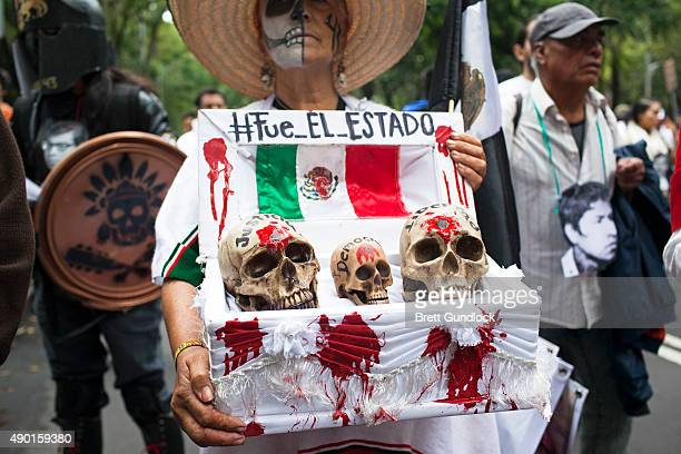 A protester holding a coffin with three skulls symbolising the death of Justice Democracy and Freedom with text on the top saying It was the State...
