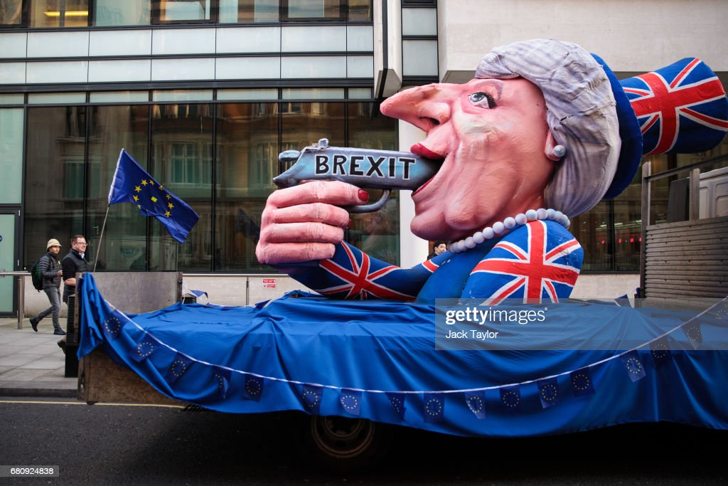 A protester holding a Flag of Europe walks past an effigy of British Prime Minister Theresa May with a gun sat outside BBC's Broadcasting House as Mrs May and her husband Philip May give a joint interview on the One Show on May 9, 2017 in London, England. Campaigning is underway ahead of the June 8th general election.