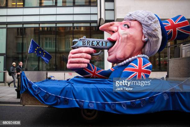 A protester holding a Flag of Europe walks past an effigy of British Prime Minister Theresa May with a gun sat outside BBC's Broadcasting House as...