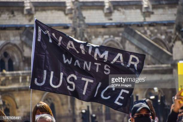 Protester holding a flag saying 'Myanmar Wants Justice' in Parliament Square during the demonstration. Demonstrators gathered to protest against the...
