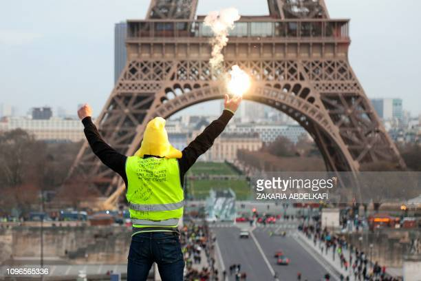 A protester holding a flare gestures in front of the Eiffel Tower during a demonstration in Paris on February 9 as the Yellow Vests protesters take...
