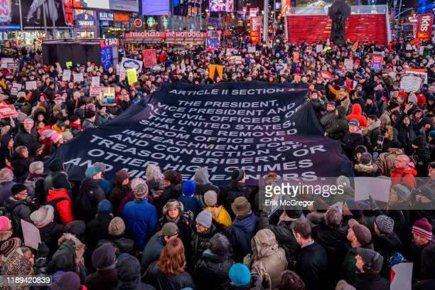 Protester holding a giant banner with impeacment articles at the rally in Times Square The night before the House of Representatives takes a somber...