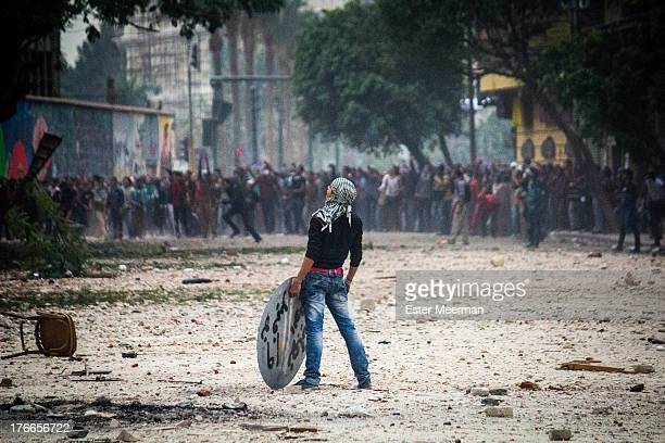 Protester holding a makeshift shield stands on Mohammed Mahmoud street in downtown Cairo, as clashes erupt between protesters and riot police on the...