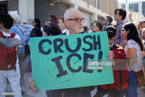 A protester holding a placard during the protest Protesters participate in a rally organized by Families Belong Together speaking out against the...