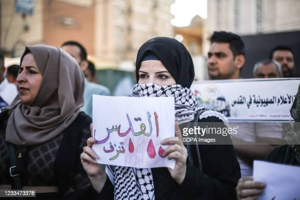 """Protester holding a placard expressing her opinion, during a demonstration in the southern Gaza Strip, against the """"flag march"""" organized by..."""