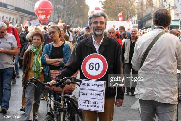 A protester holding a placard reading « 60 » for the desired pension age marchs near the Opera House during a demonstration called by pensioners'...