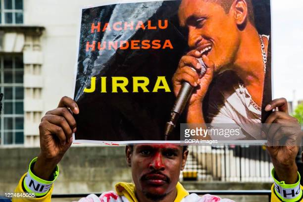 A protester holding a portrait of Haacaaluu Hundeessaa during the demonstration Ethiopian Oromo community in London protest demanding justice for...