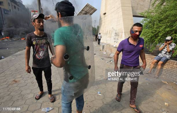 A protester holding a riot police plastic shield sprays fizzy cola drink from a bottle onto the face of another protester to relieve the effects of...