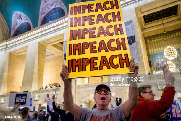 Protester holding a sign reading IMPEACH On the heels of the corrected testimony of US Ambassador to the EU Gordon Sondland admitting he delivered a...