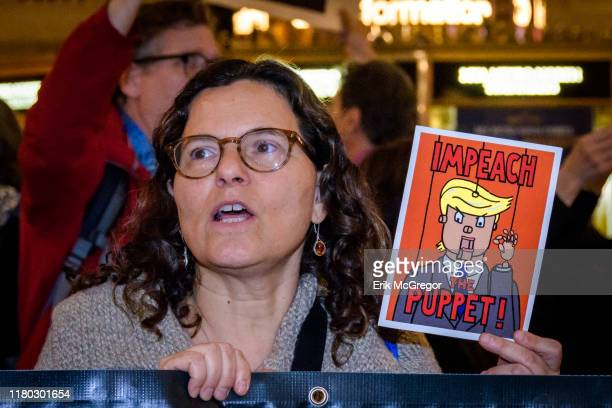 Protester holding a sign reading IMPEACH THE PUPPET On the heels of the corrected testimony of US Ambassador to the EU Gordon Sondland admitting he...