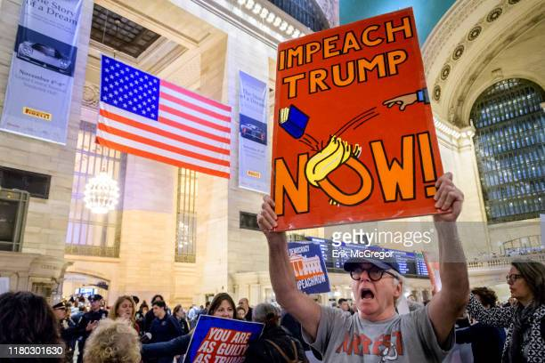 Protester holding a sign reading IMPEACH TRUMP NOW On the heels of the corrected testimony of US Ambassador to the EU Gordon Sondland admitting he...