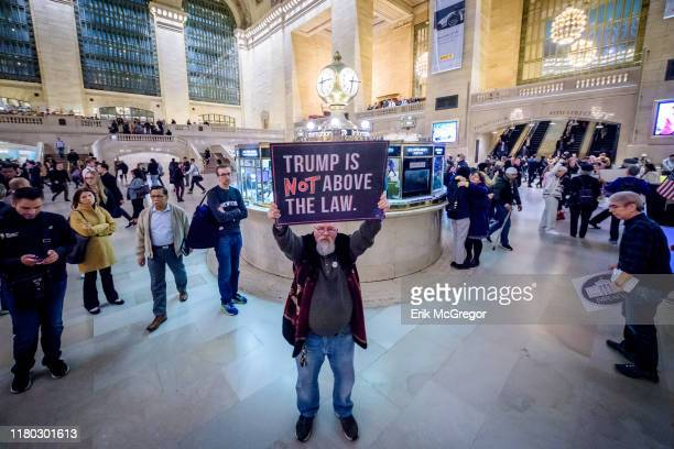 Protester holding a sign reading TRUMP IS NOT ABOVE THE LAW On the heels of the corrected testimony of US Ambassador to the EU Gordon Sondland...