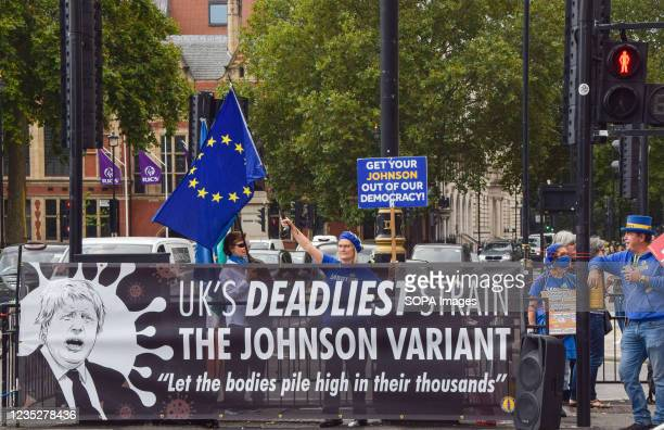 """Protester holding an anti-Boris Johnson placard and an EU flag stands behind a banner calling Boris Johnson the """"UK's Deadliest Strain"""" during the..."""