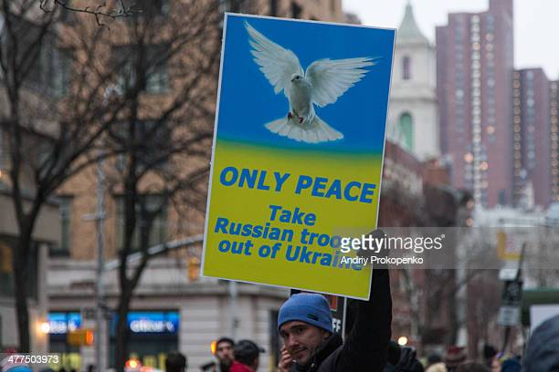 CONTENT] A protester holding an antiwar poster saying ONLY PEACE Take Russian troops out of Ukraine during a mass demonstration against Russian...