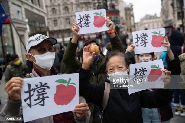 Protester holding an apple and a placard, during the demonstration. Hong Kong's national security police arrested the chief editor and four...