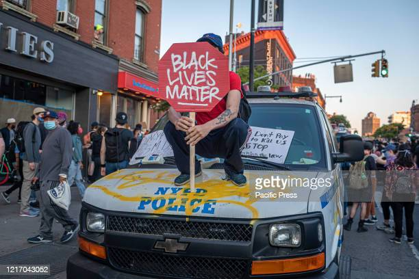 Protester holding banner joins the protest that broke out across New York City as thousands of demonstrators called for justice for George Floyd and...