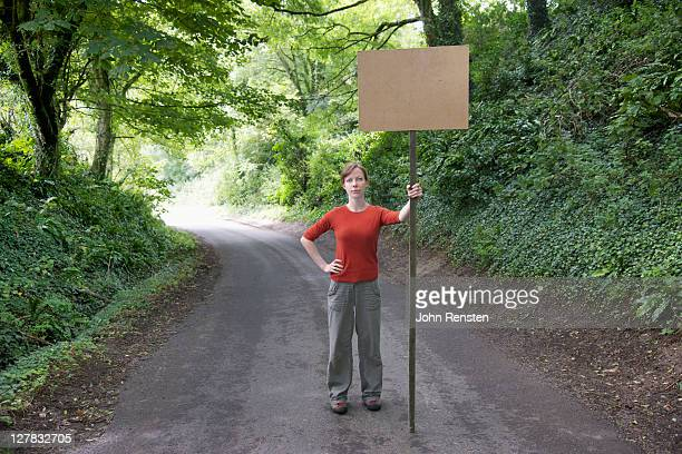protester holding blank banner on country lane - demonstrant stock-fotos und bilder