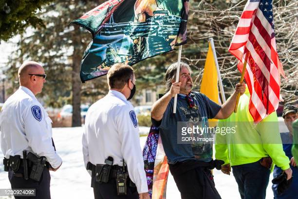 Protester holding flags walks past police officers during the demonstration. Protesters gathered at the state's legislative building to protest...