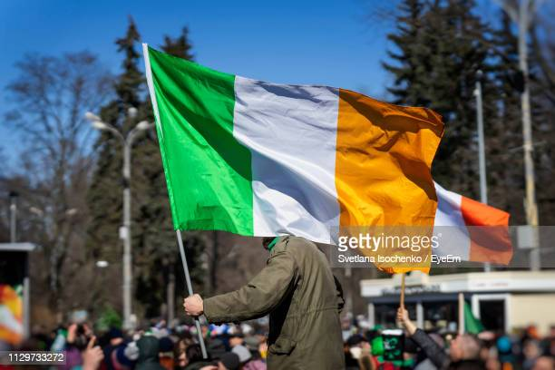 protester holding irish flag on street - irish flag stock pictures, royalty-free photos & images